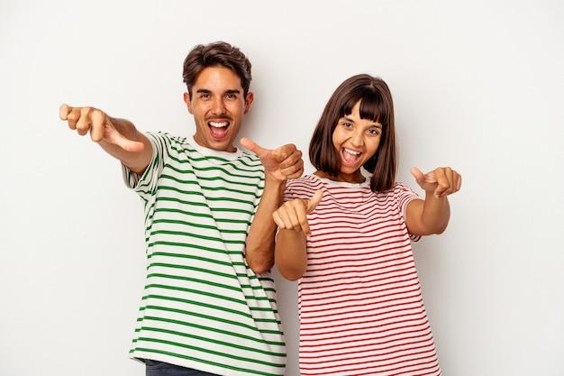 Jeune couple métis isolé sur fond blanc levant les deux pouces vers le haut, souriant et confiant.