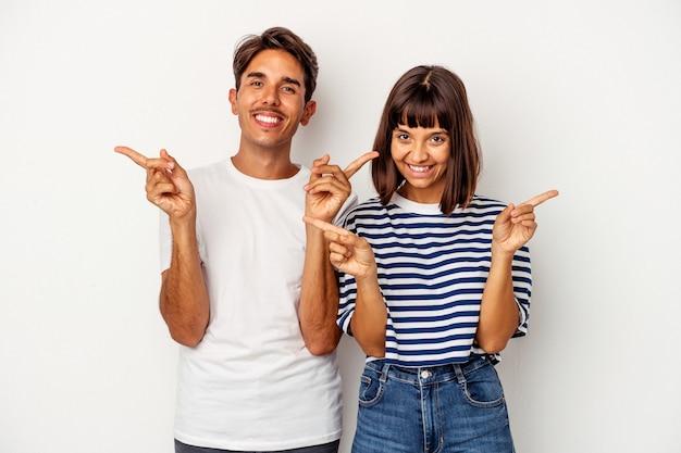 Jeune couple métis isolé sur fond blanc pointant vers différents espaces de copie, en choisissant l'un d'eux, montrant avec le doigt.