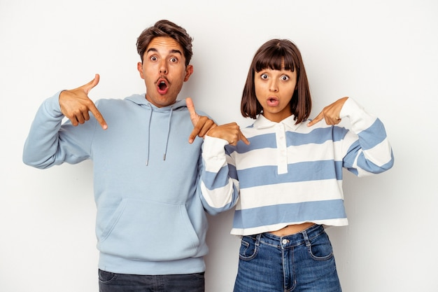 Jeune couple métis isolé sur fond blanc pointe vers le bas avec les doigts, sentiment positif.