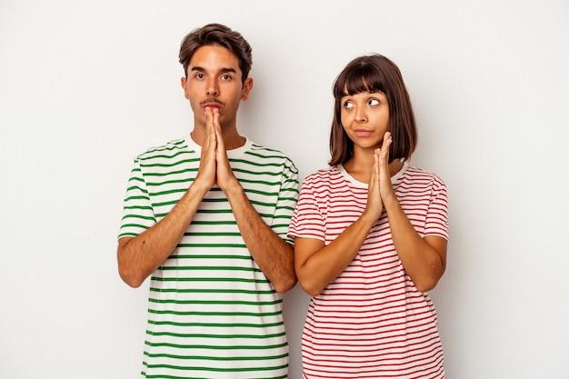 Jeune couple métis isolé sur fond blanc priant, montrant la dévotion, personne religieuse à la recherche d'inspiration divine.