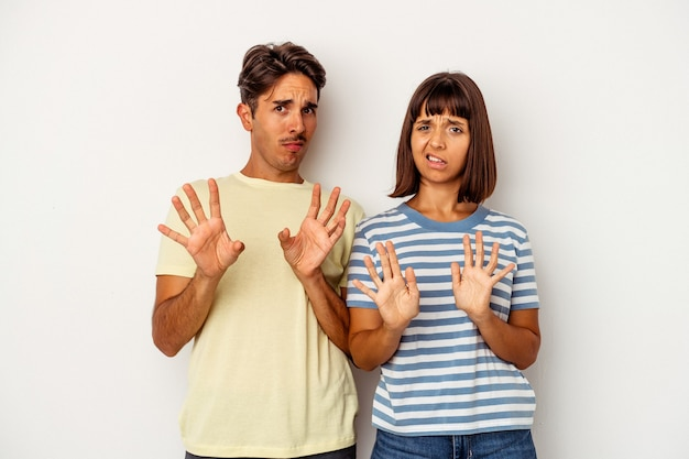 Jeune couple métis isolé sur fond blanc rejetant quelqu'un montrant un geste de dégoût.