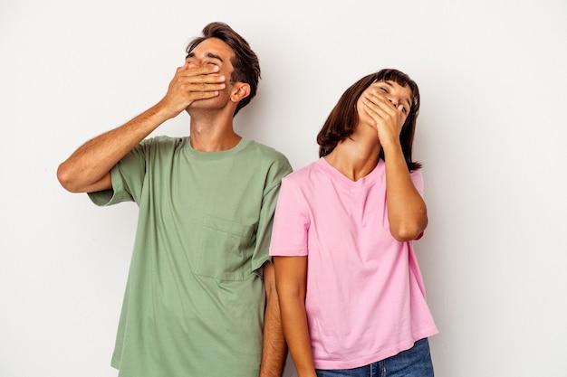Jeune couple métis isolé sur fond blanc riant heureux, insouciant, émotion naturelle.