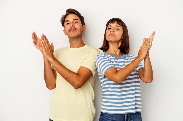 Jeune couple métis isolé sur fond blanc se sentant énergique et confortable, se frottant les mains en toute confiance.