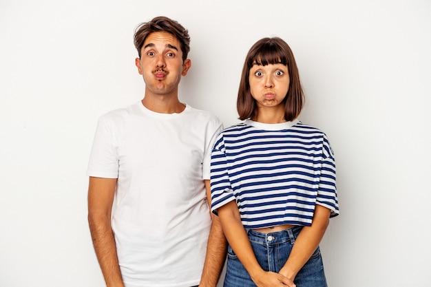 Jeune couple métis isolé sur fond blanc souffle les joues, a une expression fatiguée. concept d'expression faciale.