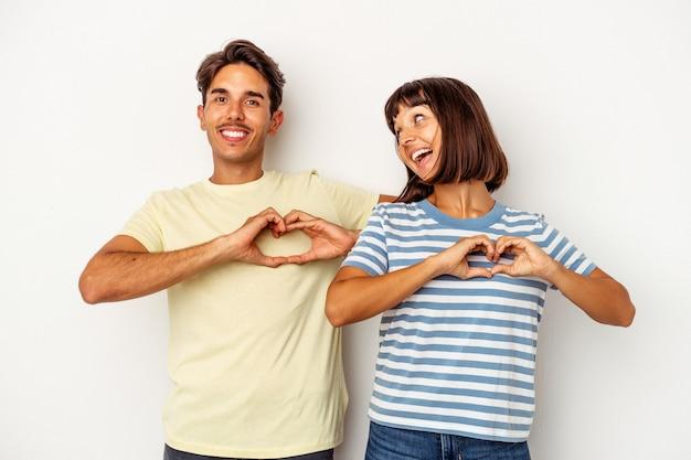 Jeune couple métis isolé sur fond blanc souriant et montrant une forme de coeur avec les mains.