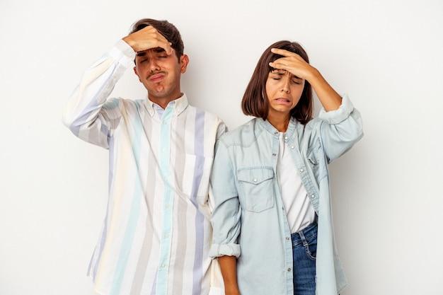 Jeune couple métis isolé sur fond blanc touchant les tempes et ayant des maux de tête.