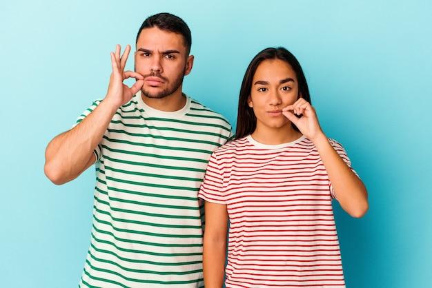 Jeune couple métis isolé sur fond bleu avec les doigts sur les lèvres gardant un secret.