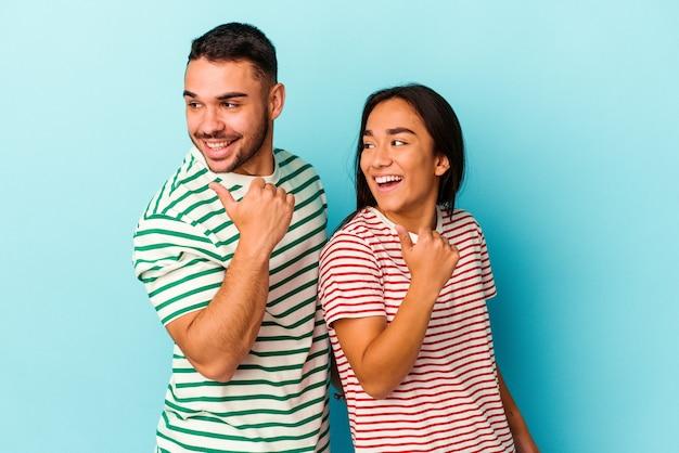 Jeune couple métis isolé sur les points de fond bleu avec le pouce, riant et insouciant.