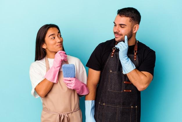Jeune couple métis nettoyant la maison isolée sur bleu détendu en pensant à quelque chose en regardant un espace de copie.