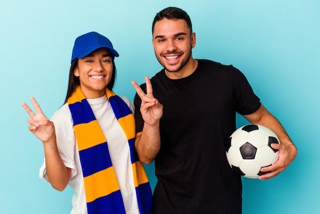 Jeune couple métis nettoyant la maison isolée sur bleu joyeux et insouciant montrant un symbole de paix avec les doigts.