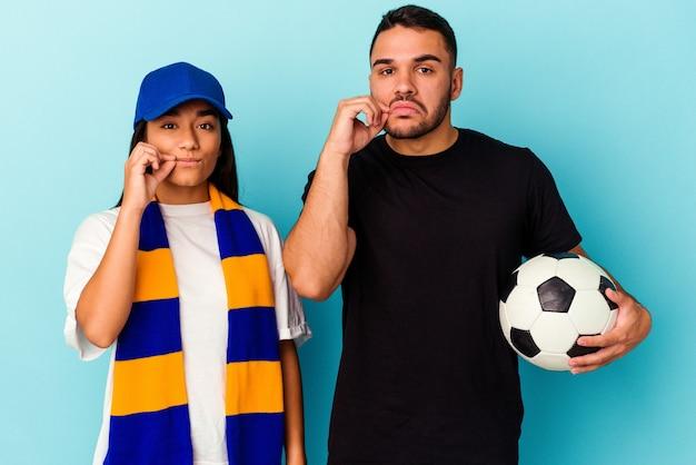 Jeune couple métis nettoyant la maison isolée sur fond bleu avec les doigts sur les lèvres en gardant un secret.