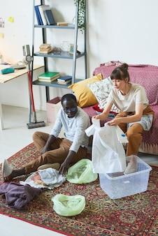 Jeune couple mettant des vêtements dans les boîtes pendant les travaux ménagers à la maison