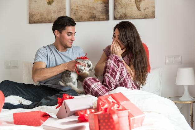 Jeune couple mignon donnant un lapin en cadeau