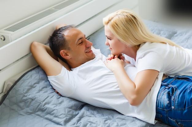 Jeune couple mignon ensemble au lit