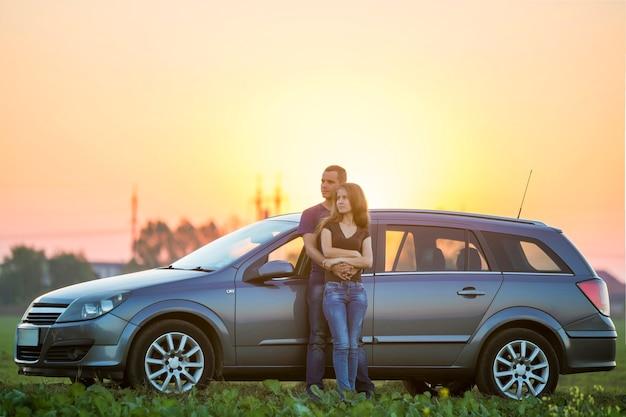 Jeune couple, mince séduisante femme aux cheveux longs et bel homme embrassé ensemble se penchant sur une voiture argentée dans un champ vert dans la campagne rurale sur un ciel lumineux au coucher du soleil ou au lever du soleil sur fond d'espace de copie.