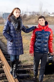 Jeune couple à la mode dans des vêtements d'hiver chauds debout sur une ligne de chemin de fer avec la fille tenant l'épaule de son petit ami alors qu'elle se tient en équilibre sur la piste