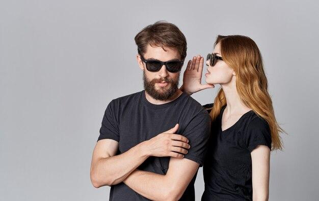 Jeune couple de mode portant des lunettes de soleil bavardant hug romance studio espace isolé