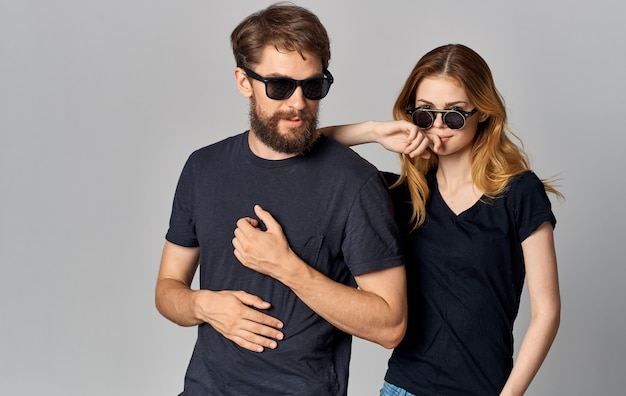 Jeune couple de mode portant des lunettes de soleil bavardant hug studio de romance isolé.