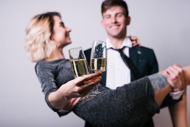 Jeune couple montrant des coupes de champagne