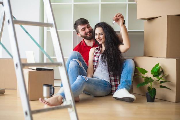 Jeune couple montre les clés du nouvel appartement