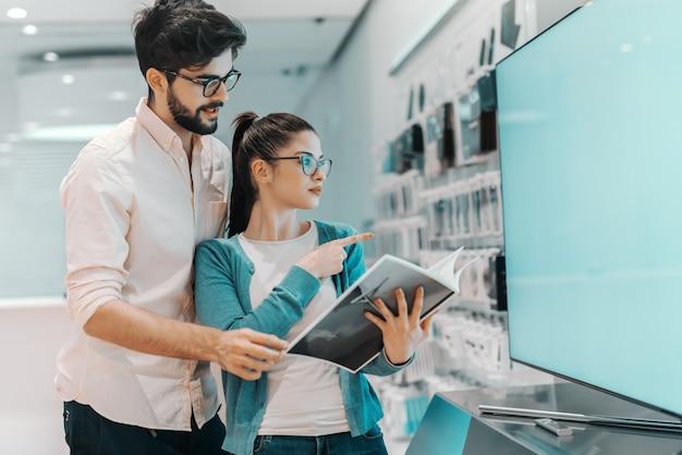 Jeune couple multiculturel attrayant à la recherche d'une nouvelle télévision à écran plasma. femme tenant la brochure et pointant vers la télévision tandis que l'homme la serrant dans ses bras.
