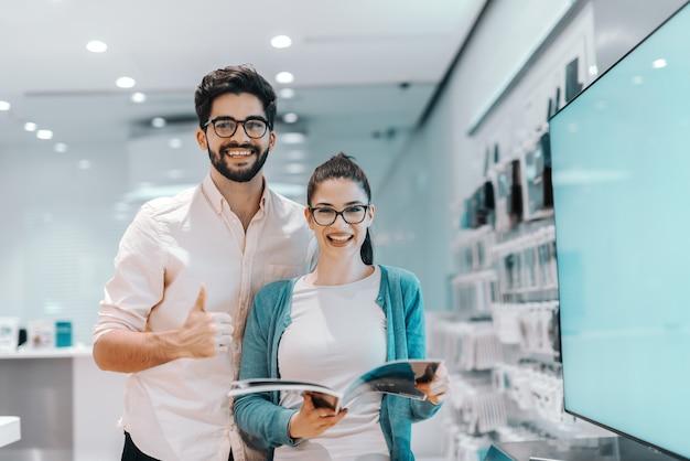 Jeune couple multiculturel attrayant à la recherche d'une nouvelle télévision à écran plasma. femme tenant la brochure tandis que l'homme tenant les pouces vers le haut.