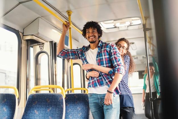 Jeune couple multiculturel étreignant dans les transports publics.