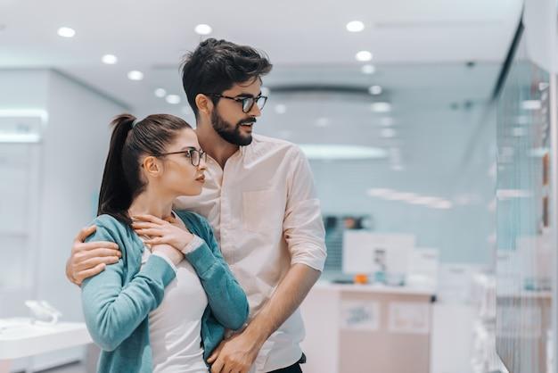 Jeune couple multiculturel séduisant et impressionné à la recherche de nouveaux téléviseurs à écran plasma qu'ils veulent acheter. intérieur du magasin technique.