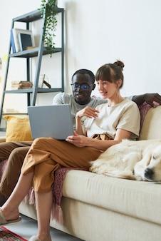 Jeune couple multiethnique assis sur un canapé en train de regarder quelque chose sur un ordinateur portable et souriant, ils passent du temps à la maison