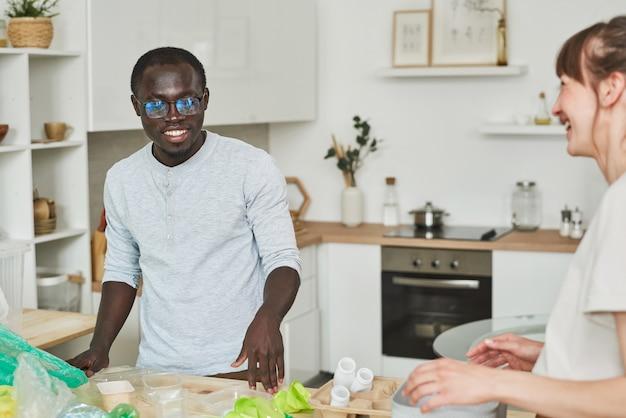 Jeune couple multiethnique nettoyant la maison et jetant les ordures dans la cuisine