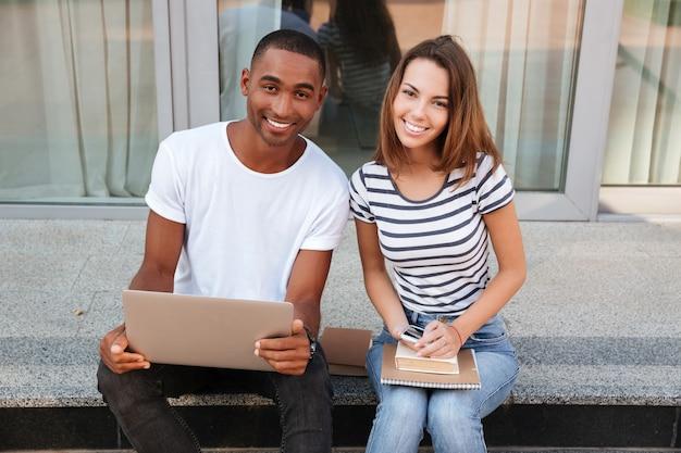 Jeune couple multiethnique souriant utilisant un ordinateur portable à l'extérieur ensemble
