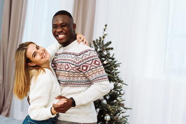 Un jeune couple multinational danse, rit à côté de l'arbre de noël. joli couple dansant dans le salon, célébrant le réveillon de noël.