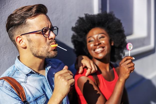 Jeune couple multiracial attrayant appuyé sur le mur et lécher des sucettes.