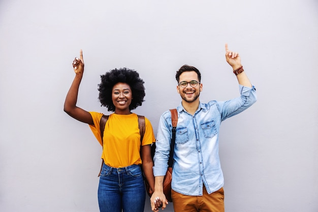 Jeune couple multiracial attrayant tenant par la main et pointant vers le haut.
