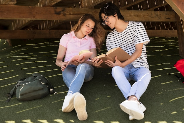 Jeune couple multiracial, lire, livres, dans parc
