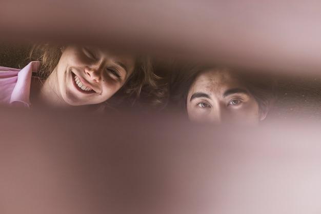 Jeune couple multiracial regardant à travers des planches en bois