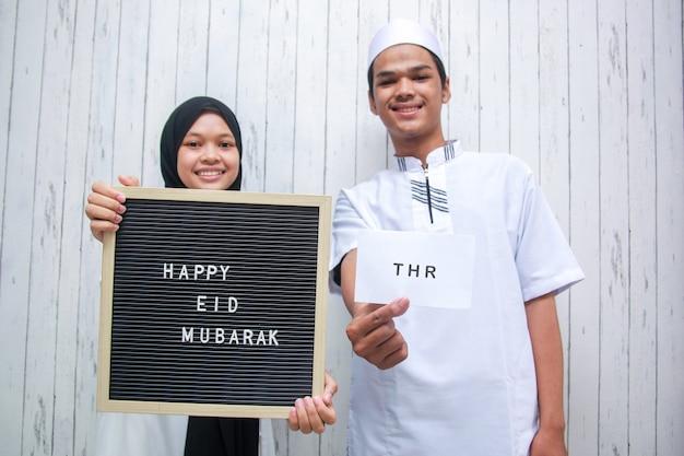 Jeune couple musulman tenant une enveloppe blanche appelée thr tunjangan hari raya et un tableau aux lettres dit joyeux eid mubarak