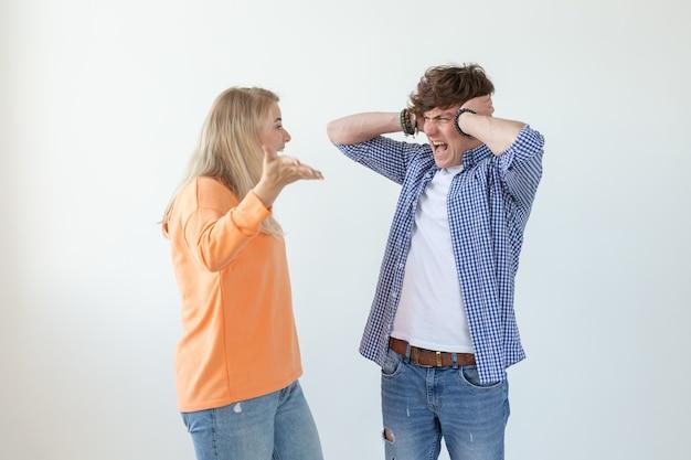 Jeune couple nerveux méchant fille mignonne et bouleversé jeune mec bouchant les oreilles maudissant debout contre