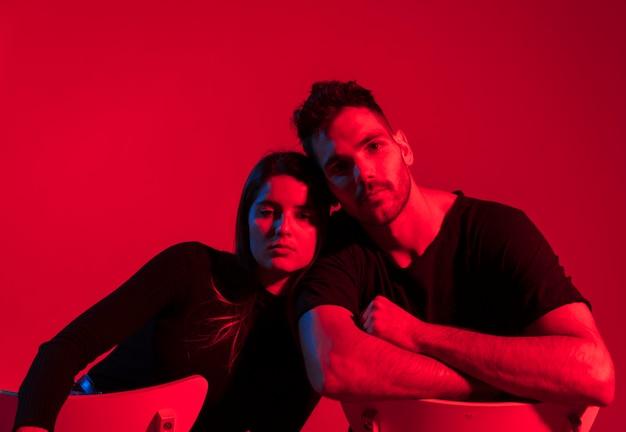 Jeune couple en noir assis sur des chaises