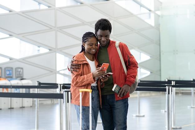 Jeune couple noir avec des bagages vérifiant son téléphone portable dans un aéroport vide