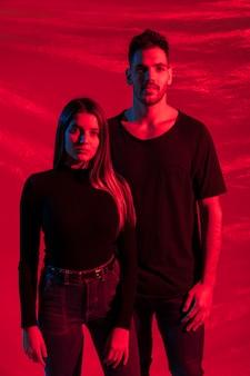 Jeune couple en noir debout sur fond rouge