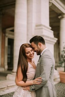Jeune couple nouvellement marié qui pose à rome avec une belle et ancienne architecture en arrière-plan