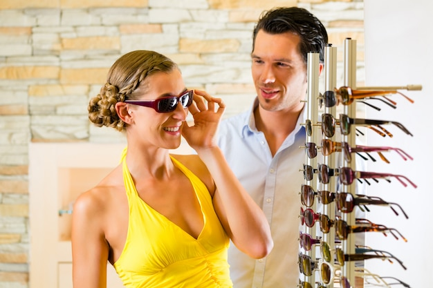 Jeune couple à l'opticien avec des lunettes