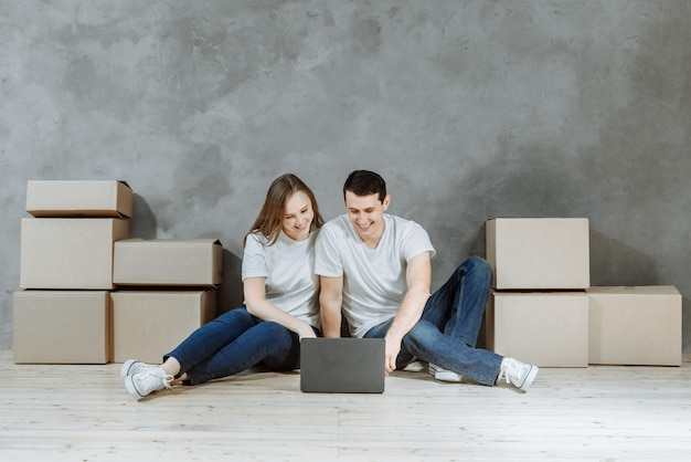 Jeune couple avec ordinateur portable en appartement parmi les boîtes de corton.