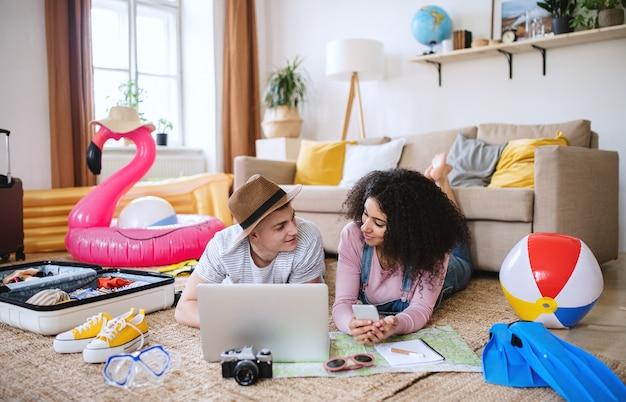 Jeune couple avec ordinateur portable pour les vacances d'été à la maison, parlant.