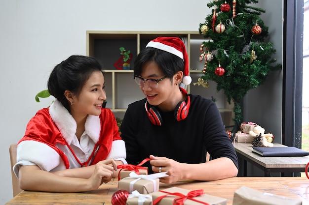 Jeune couple ouvrant le cadeau de noël dans le salon.