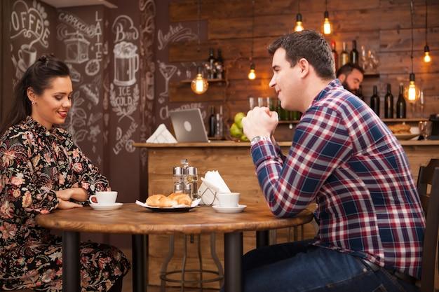 Jeune couple parlant de l'avenir dans un pub vintage confortable. sortie nocturne.
