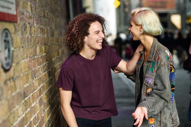 Jeune couple parlant en contexte urbain dans une rue typique de londres.