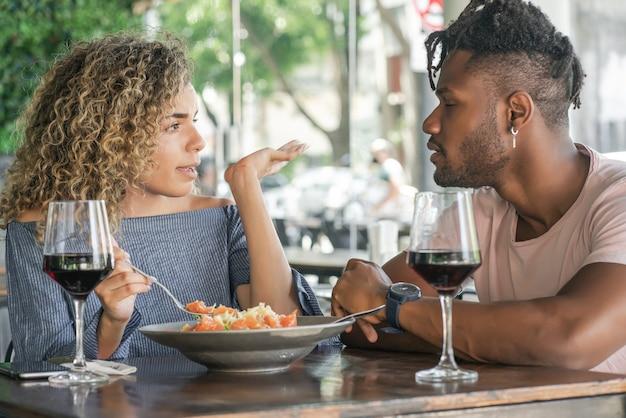 Jeune couple parlant et profitant tout en déjeunant ensemble dans un restaurant.
