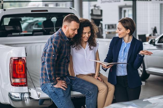Jeune couple parlant à un vendeur dans une salle d'exposition